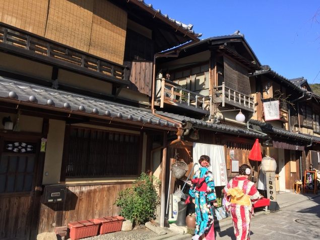 Two girls in very vibrant kimonos walking in front of traditional Japanese homes in Sannenzaka Ninenzaka area in Kyoto, in Japan