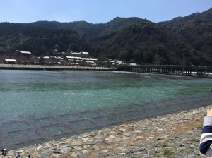Katsura River, in Arashiyama. A beautiful wide, crystal clear river, with a traditional wooden foot bridge, some buildings and a forested hill in the background.