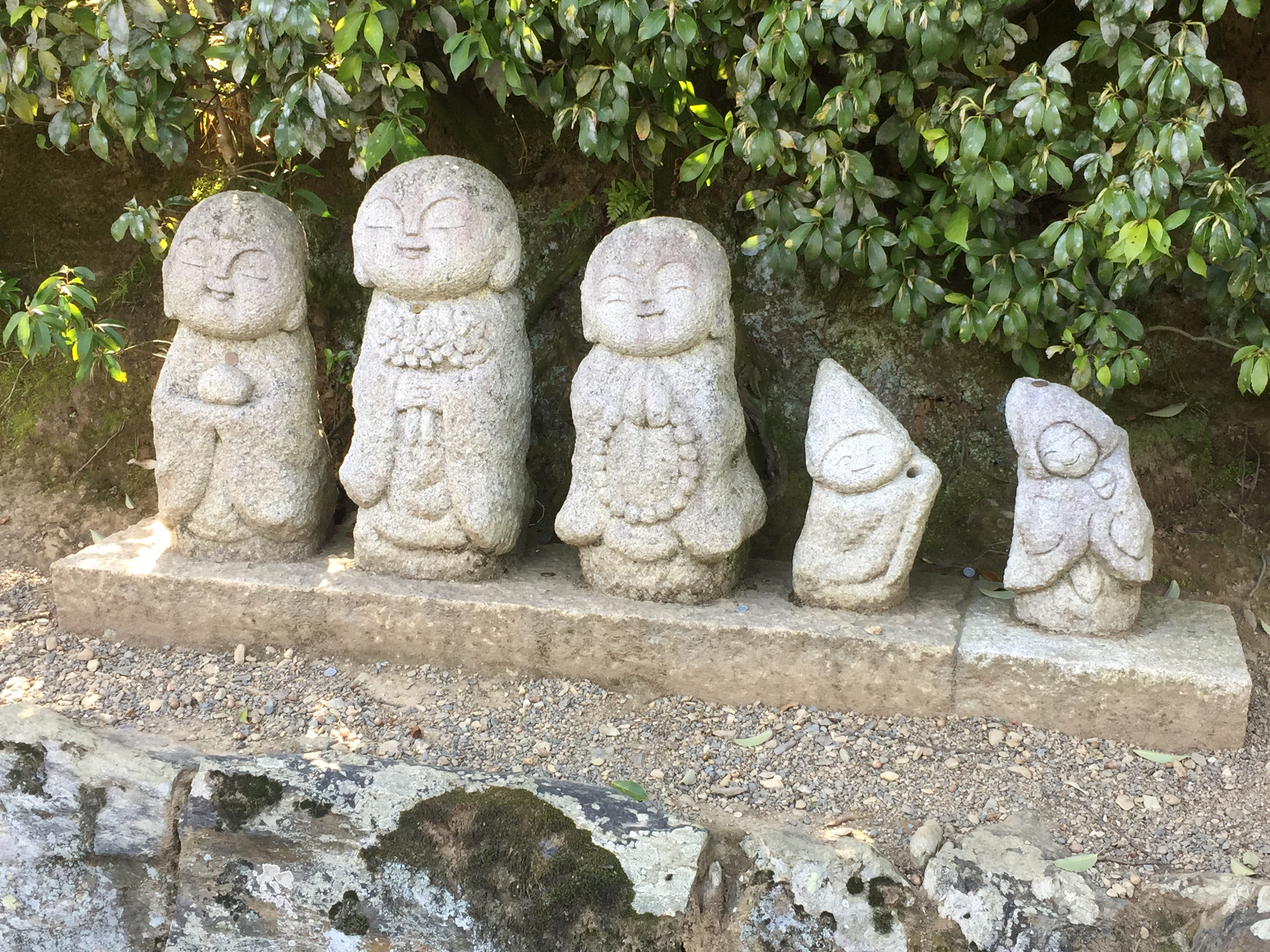 Small stone jizo statues on the side of a path in Arashiyama in Kyoto, in Japan.