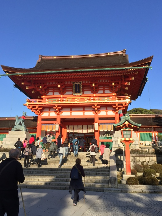 Giant vermillion gateway at Fushimi Inari temple in Kyoto, in Japan. There are large stone fox statues, lanterns and many people.