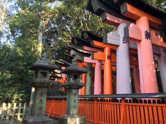 Many vermillion tori gates, standing close together, with a red picket fence and several stone lanterns in the forest at Fushimi Inari temple in Kyoto.