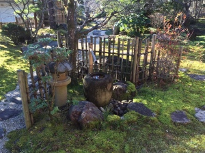 beautiful Japanese garden with bamboo fence, lantern and stone water feature