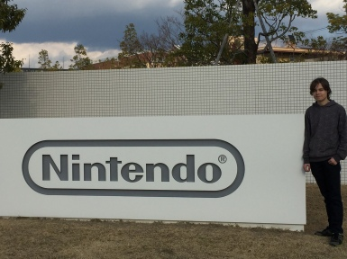 Boy standing next to giany Nintendo sign at Nintendo headquarters