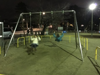 two girls on swings in a park in Kyoto late at night