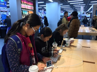 three girls playing on iphones at an apple counter in Yodabashi Camera in Kyoto