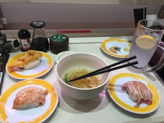 sushi train restaurant, yellow plates with assorted sushi, a bowl of udon noodles and a glass of yuzu soda shibuya tokyo