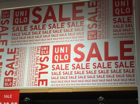 A billboard with Sale written many times in red going all different directions