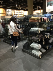 Japanese sweater display at Muji in Chadstone, with shopper looking at products
