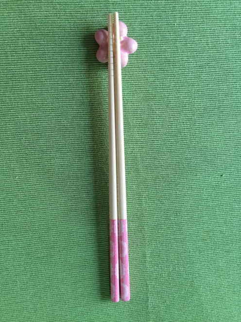 pink hashi (chopsticks) resting on sakura rest
