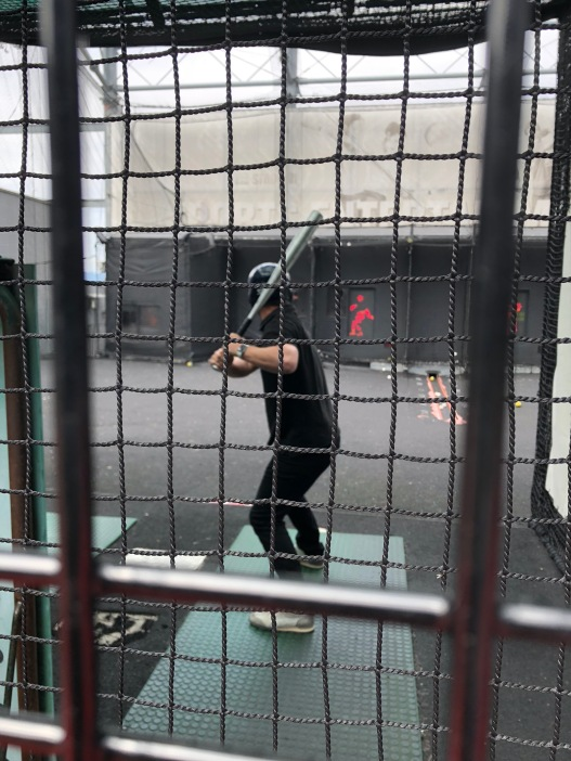 Super Sake Boy playing baseball, with a pitching machine, in nets at a games centre in Kyoto. He is swinging the bat.