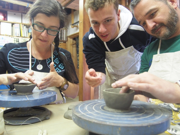 Super Sake Boy and Blossomkitty doing pottery in a tradition potter's studio in Higashiyama, in Kyoto, in Japan. Working on clay wheels, making small sake cups. Ewan is assisting with the design.