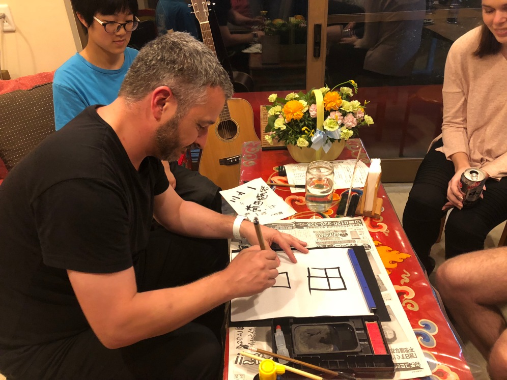 Super Sake Boy doing kanji calligraphy in Kyoto at Guesthouse Soi