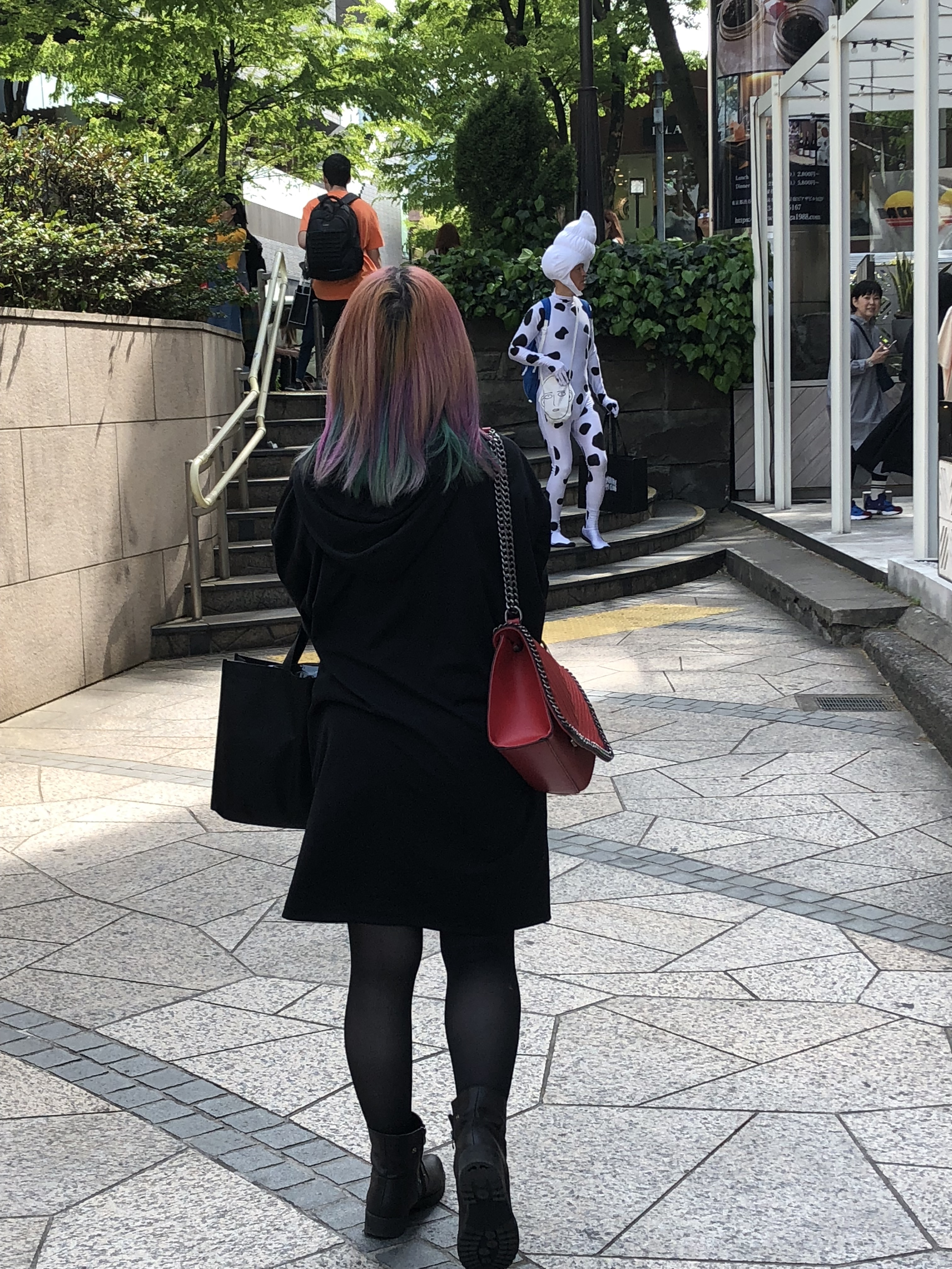 A girl with orange, blue and pink hair walking in Harajuku, with a man dressed in a lycra cow print onesie and an ice-cream swirl headpiece, in the background