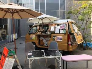 An old VW kombi van in Harajuku, in Tokyo, selling coffee. It is very decorated and has a card table and some chairs under a cafe umbrella in front of it.