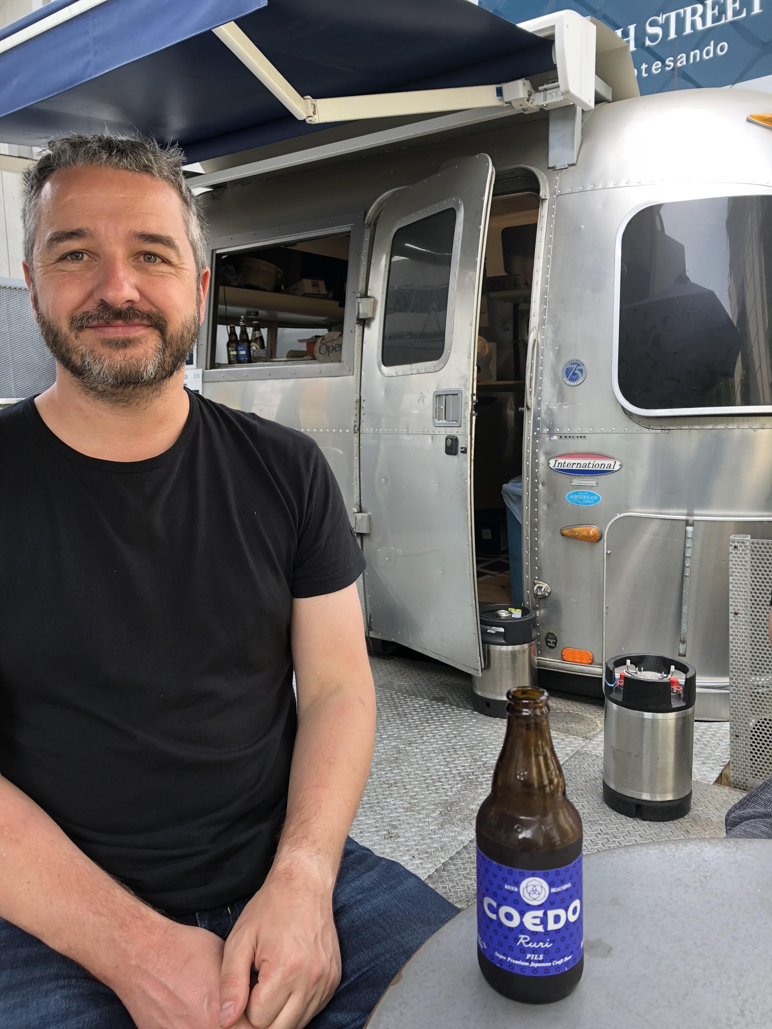 Super Sake Boy drinking a Coedo Beer in Harajuku in Japan, in front of an Airstream caravan