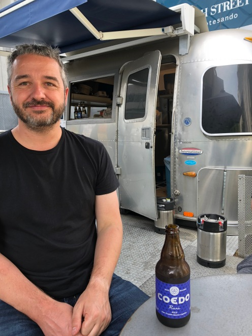 Super Sake Boy drinking a Coedo Beer in Harajuku in Japan, in front of an Airstream caravan
