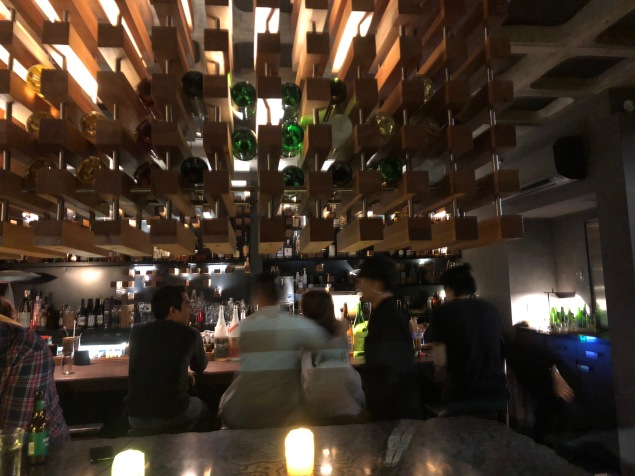 Funky Japanese sake bar in Spring street, Melbourne. Wooden hanging bottle racks with sake and people drinking at the bar.