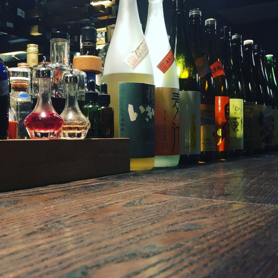 A row of 1.8 litre sake bottles on a wooden bar with colourful labels and Kanji