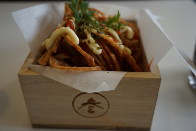 Renkon, or lotus root chips in a masu, traditional wooden box for measuring rice and drinking sake, with sriracha and kewpie mayo drizzled over the top and shredded nori and dill garnishing