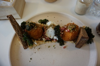 A beige plate on a table with pumpkin croquette special, with miso hummus, crispy kale, poached egg, pomegranate and Japanese dukkah