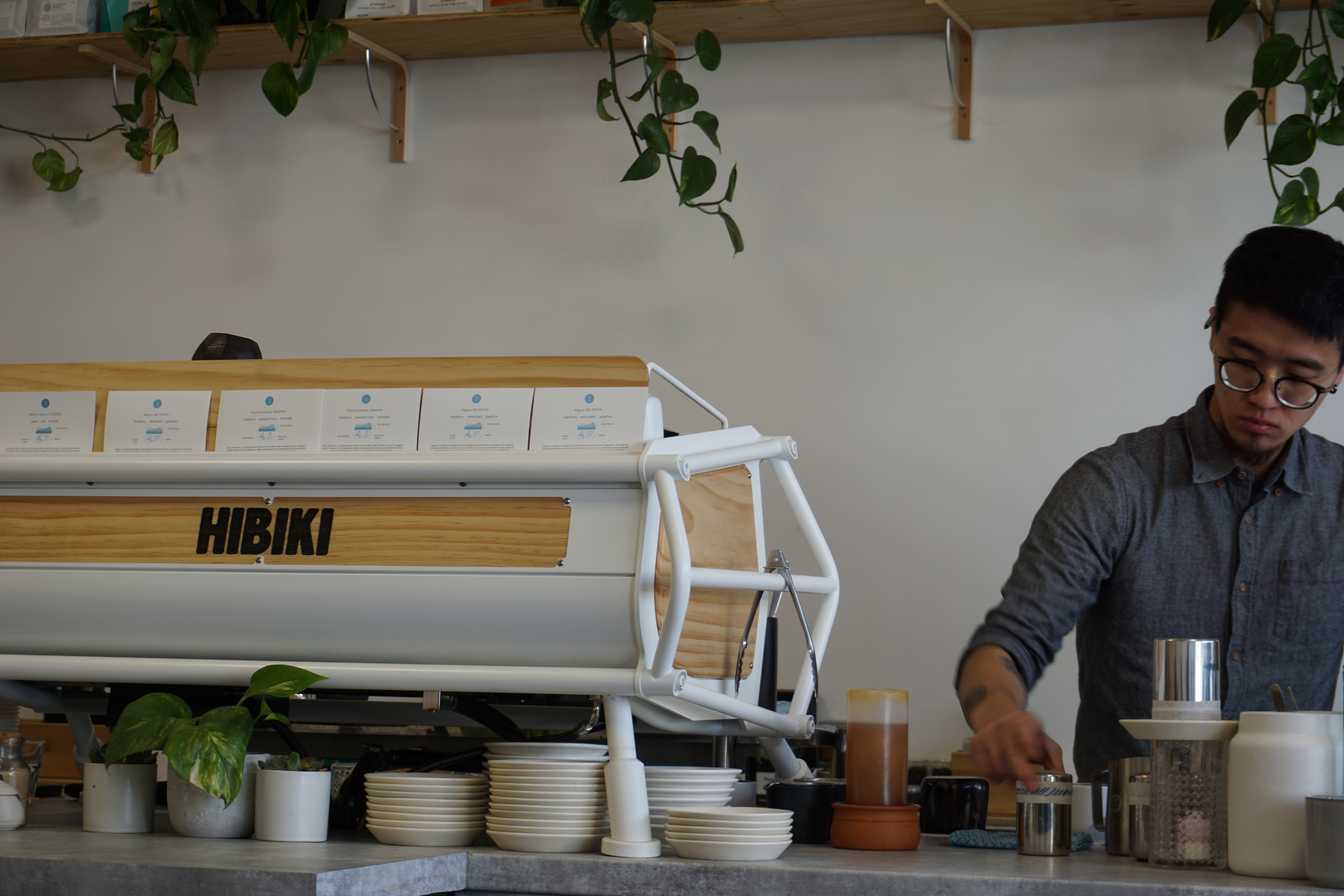 Funky, retro coffee machine in an ultra modern cafe, with a Japanese barista making coffee behind the concrete bar, in a Japanese cafe in Melbourne