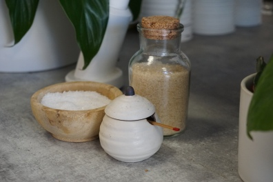 Small Japanese style jars and pinch pots with salt and sugar and shichimi on a concrete bar