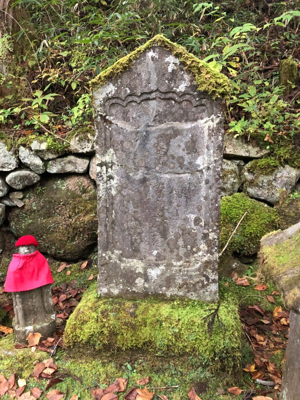 A very old stone marker that all the writing has worn away from, the base covered in moss and with a small Jizo statue along side. A dry rock wall is behind the statue and marker. Nikko, Japan.