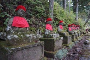 A row of old, stone, sitting Jizo statues, with red bonnets and bibs and covered in moss. They sit on pedestals, along a very old cobblestone path, overlooking Kanmangafuchi Abyss in Nikko, Japan
