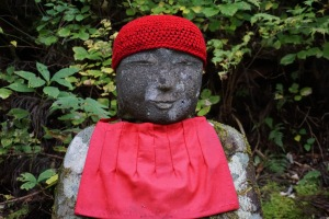 A close up of a serenely smiling Jizo statue, with a red crocheted bonnet and a bib apron, in Nikko, Japan