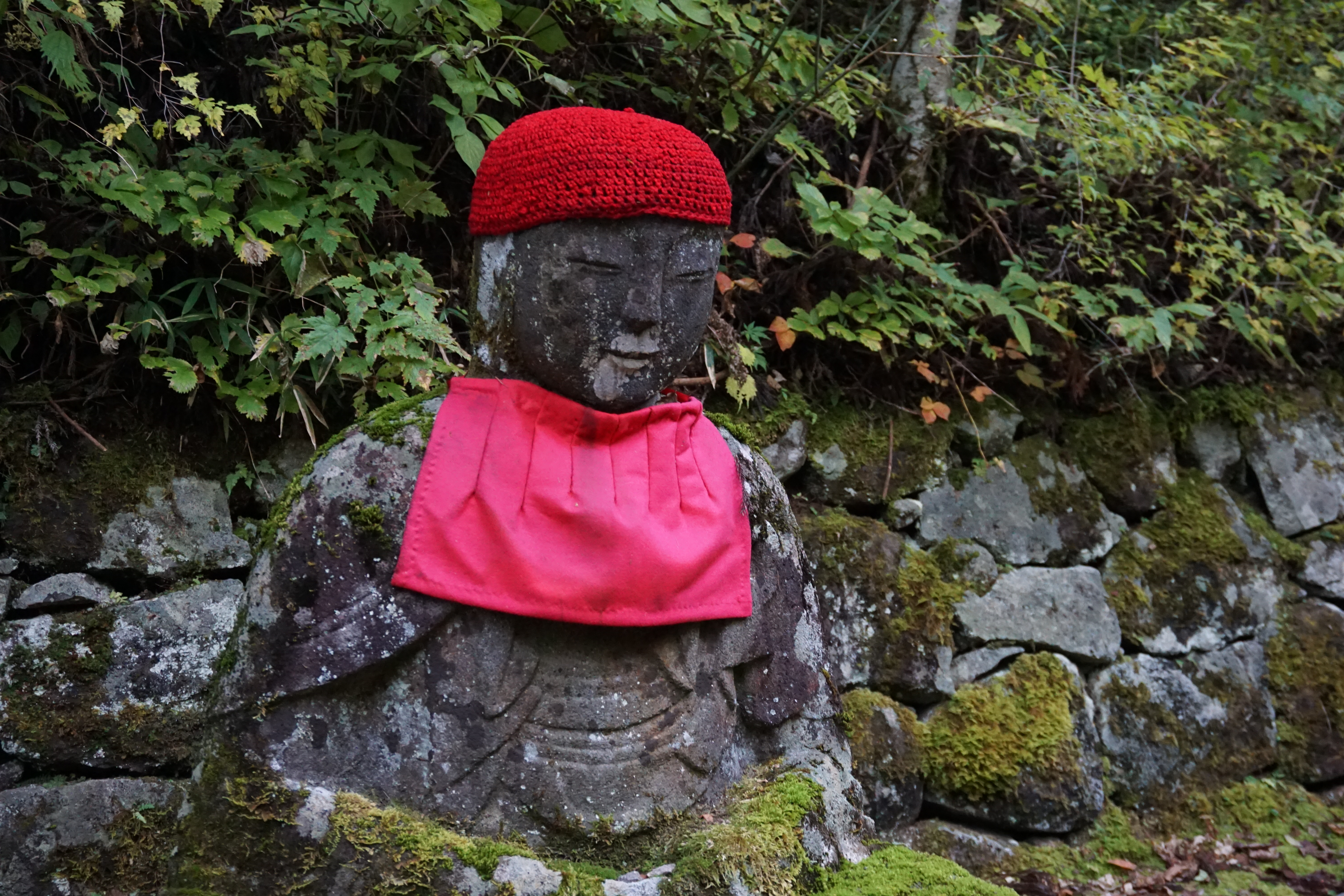 Stone Jizo statue with a red crocheted cap and a bib, apron, sitting in the forest in Nikko, surrounded by moss covered rocks