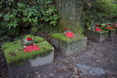 Stone pedestals that Jizo states used to sit on, but the statues have been worn away over time. The bonnets and aprons remain, along with some rocks and a lot of moss