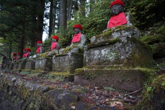 A row of seated stone Jizo statues, with red crocheted bonnets and bib aprons, sitting on pedestals with kanji and surrounded with moss, trees and plants. In Nikko, Japan