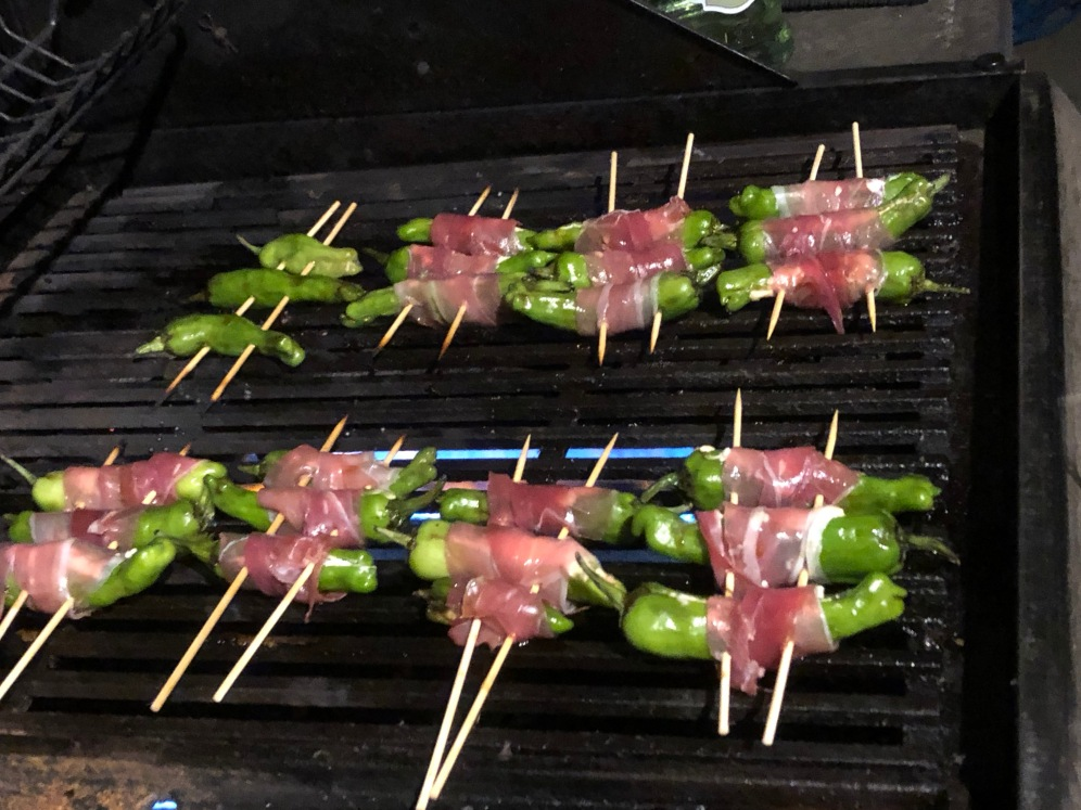 Japanese shishito peppers wrapped in prosciutto grilling on a bbq grill