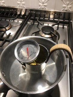 Sake with thermometer in a saucepan, on a hob. Sake is in a pewter tanpo.