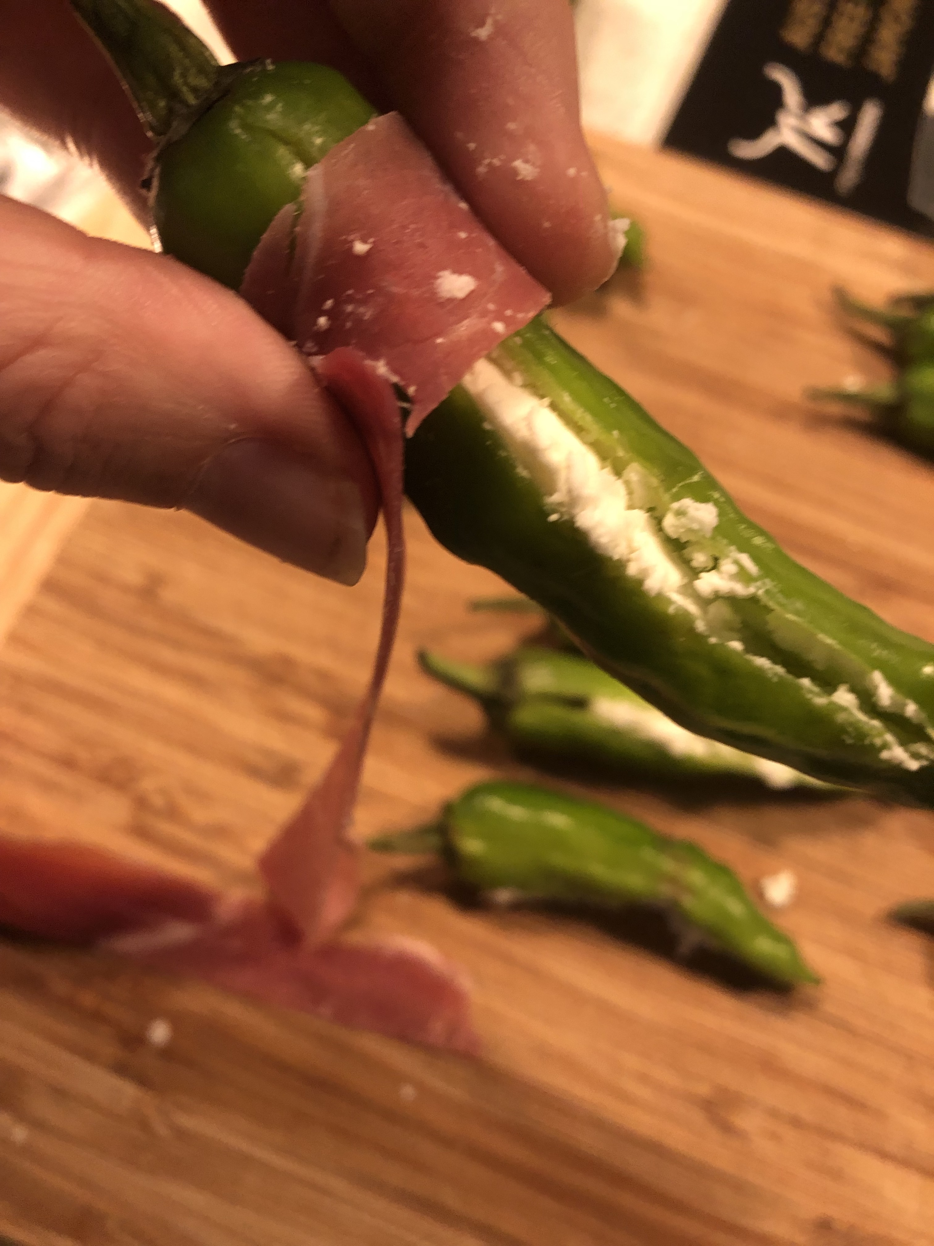 Japanese shishito pepper, cut down the centre and stuffed with goats cheese being wrapped in prosciutto
