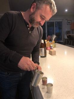 Super sake boy pouring warmed sake from pewter tanpo into pewter ochoko