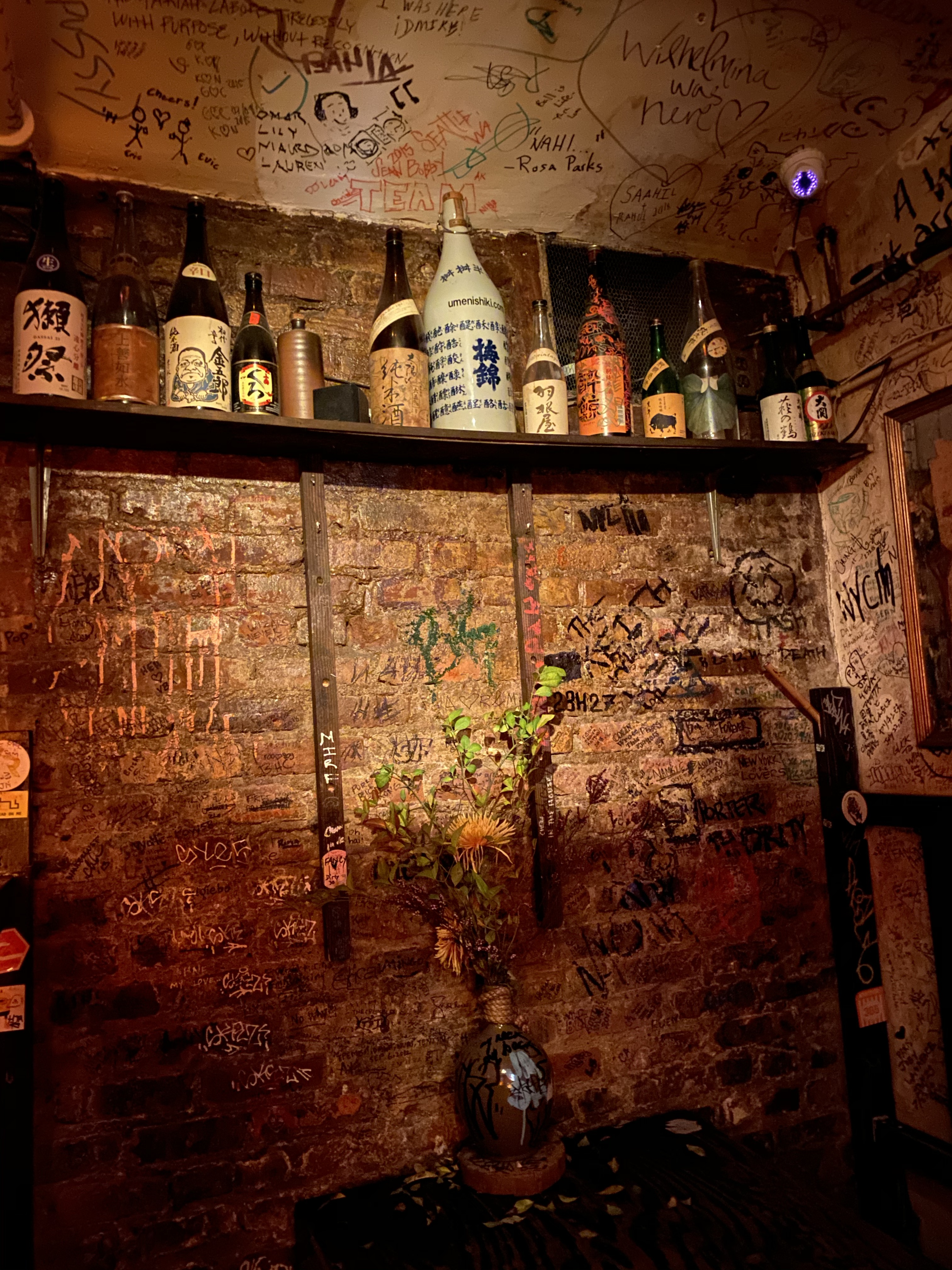Shelf with sake bottles at Sake Bar Decibel