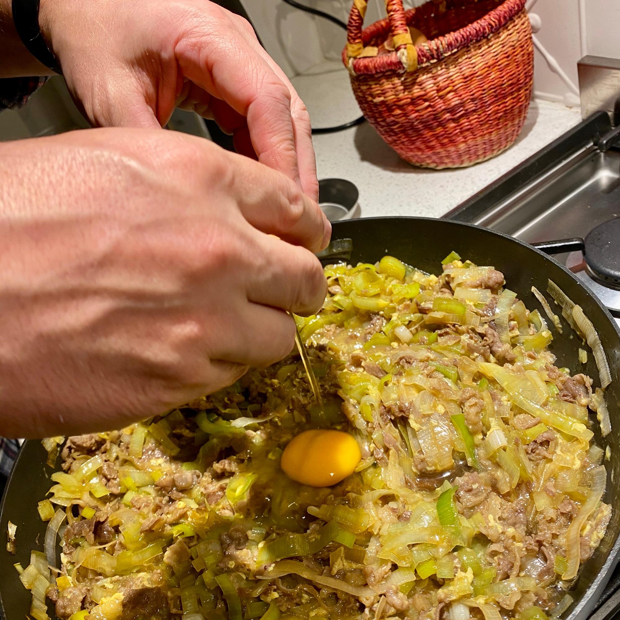 Cracking an egg into the sukiyaki